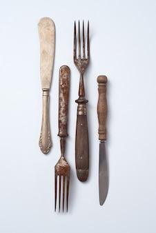 Komposition aus metallischen alten messern und gabeln mit holzgriffen auf grauem hintergrund mit platz für text. vintage sammlung. flach liegen