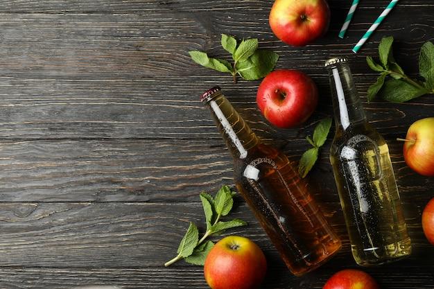 Komposition mit apfelwein, äpfeln und strohhalmen auf holztisch