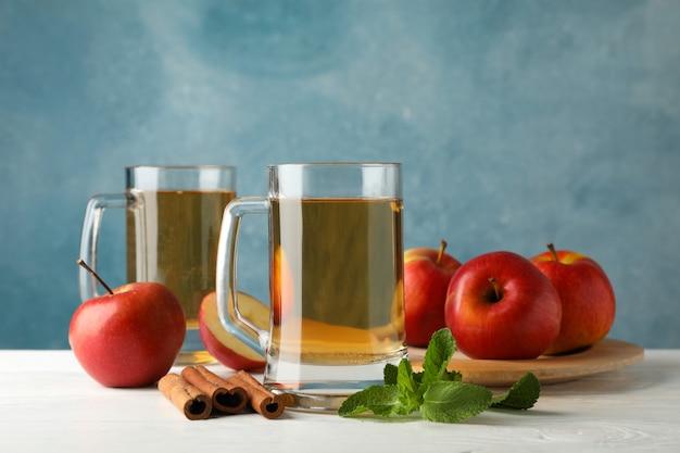 Komposition mit apfelwein, zimt und äpfeln auf weißem holztisch