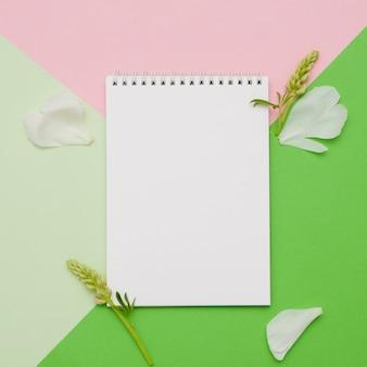 Komposition mit blumen und notebook mit geometrischen formen