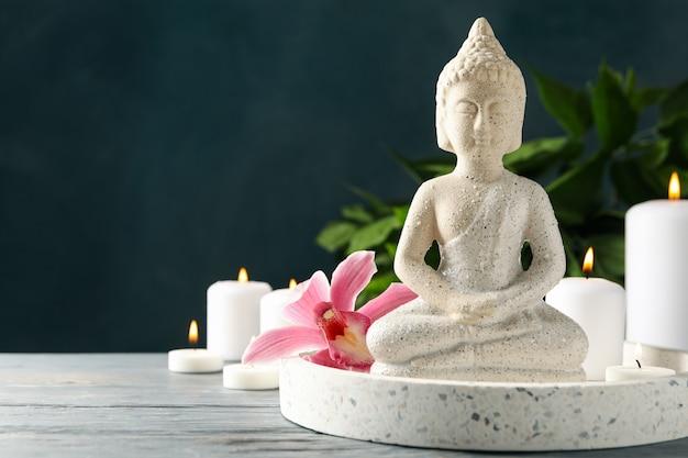 Komposition mit buddha und kerzen auf holztisch. zen-konzept
