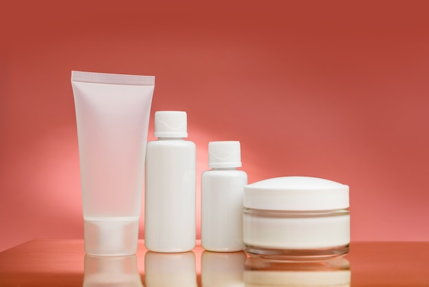 Komposition mit cosplay-produkten auf rosa hintergrund mit kopierraum. tuben und blasen für kosmetika auf einer glänzenden oberfläche.