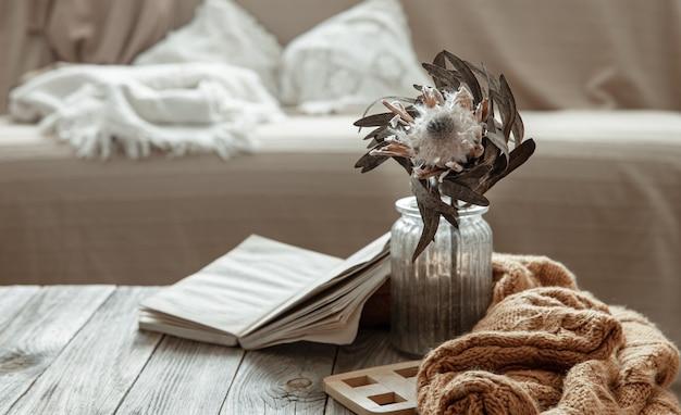 Komposition mit einem buch, einer trockenblume und einem strickelement im inneren des raumes.