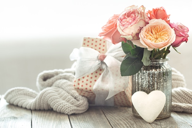 Komposition mit einem rosenstrauß in einer glasvase mit geschenkbox