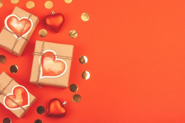 Komposition mit geschenkboxen und konfetti auf rot. hintergrund mit kopienraum für valentinstag.