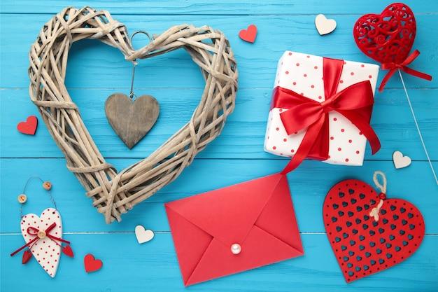 Komposition mit geschenken, roten herzen und rose auf blauem holz