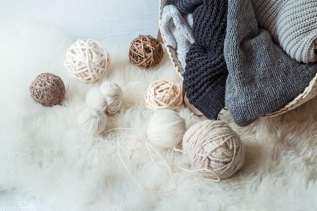 Komposition mit gestrickten pullovern und einem fadenballen