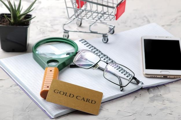 Komposition mit goldkarte, notebook, smartphone, brille, pflanze, lupe und einkaufswagen