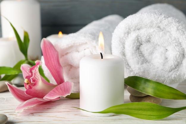Komposition mit kerzen, handtüchern, steinen und orchideen auf holztisch. zen-konzept