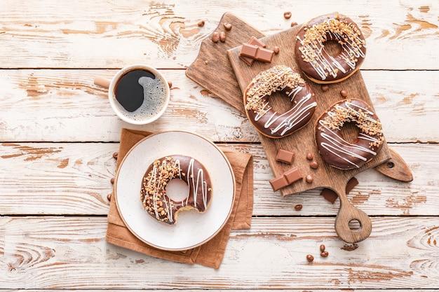 Komposition mit leckeren donuts und kaffee auf dem tisch