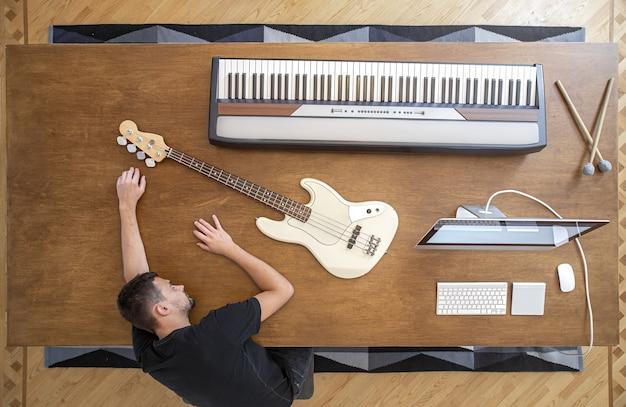 Komposition mit musikinstrumenten auf einem großen holztisch in einem tonstudio.