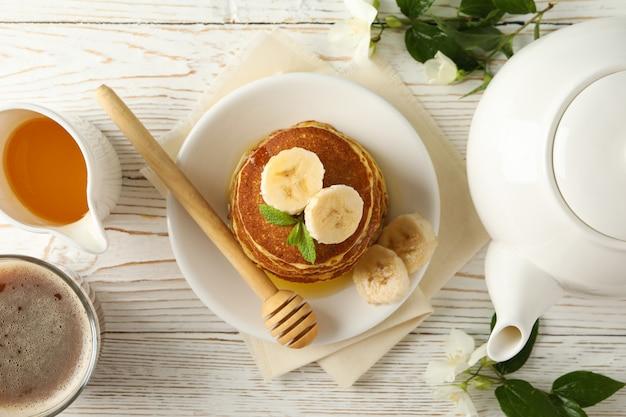 Komposition mit pfannkuchen auf weißem holzraum, draufsicht. süßes frühstück