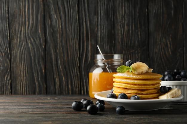 Komposition mit pfannkuchen, banane, blaubeere und marmelade auf holzfläche