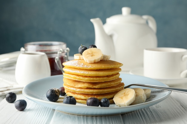 Komposition mit pfannkuchen, banane und blaubeere auf holztisch. süßes frühstück