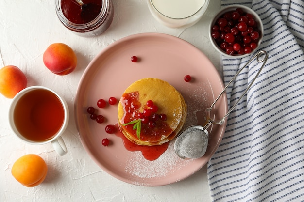 Komposition mit pfannkuchen mit marmelade und cranberry auf weißem raum