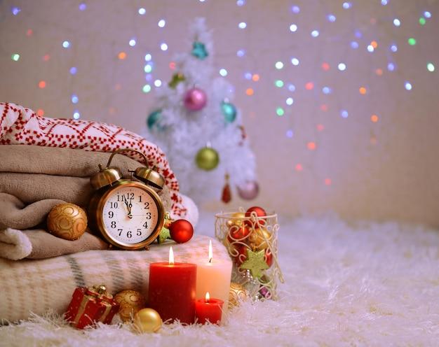 Komposition mit plaids, kerzen und weihnachtsschmuck, auf weißem teppich