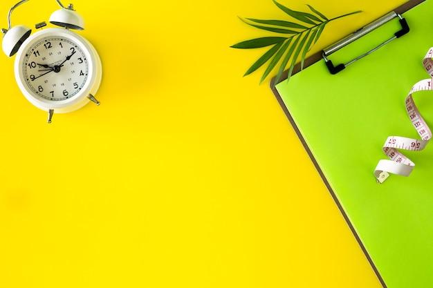 Komposition mit platte, wecker und maßband auf farbigem hintergrund. diätkonzept und gewichtsverlustplan, kopierraum