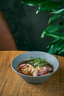 Komposition mit ramen-suppe mit rindfleisch in grauer platte auf holzuntergründen