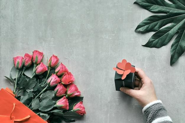 Komposition mit rosenstrauß und exotischem pflanzenblatt