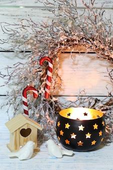 Komposition mit schönen kerzenständern, weihnachtskranz und anderen dekorationen für die inneneinrichtung auf holzhintergrund