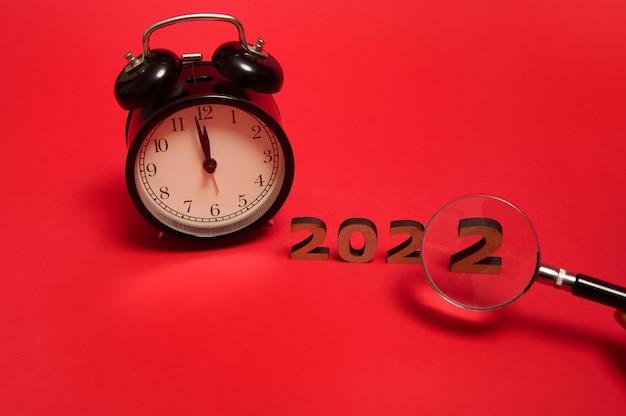 Komposition mit schwarzem wecker mit mitternacht auf dem zifferblatt und abgeschnittener hand mit lupe, die die nummer zwei der holzziffern 2022 zeigt. neujahrskonzept isoliert auf rotem hintergrund