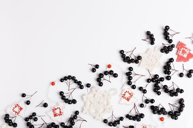 Komposition mit schwarzen aroniabeeren, weiß-rotem dekor, gestrickten schneeflocken auf weißem hintergrund. konzept von weihnachten, winter, neujahr, jahreszeitenwechsel. ansicht von oben, flach, kopienraum