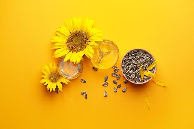 Komposition mit sonnenblumenöl und samen auf gelb