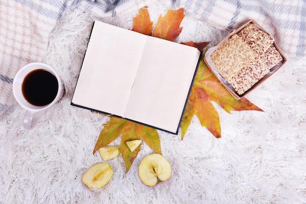 Komposition mit warmem plaid, buch, tasse heißem getränk, auf farbigem teppichhintergrund