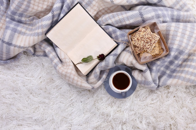 Komposition mit warmem plaid, buch, tasse heißgetränk auf farbteppichhintergrund carpet