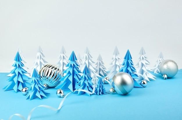 Komposition mit weihnachtsbäumen und kugeldekorationen aus blauem und weißem papier