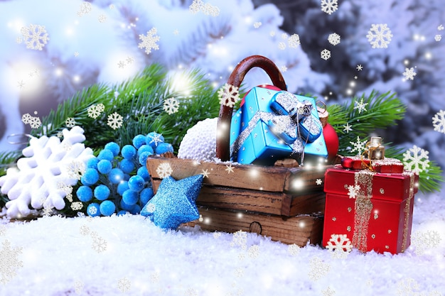 Komposition mit weihnachtsschmuck im korb, tannenbaum auf hellem hintergrund