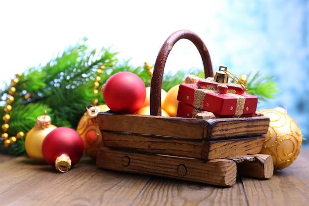 Komposition mit weihnachtsschmuck im korb, tannenbaum auf holztisch, auf hellem hintergrund