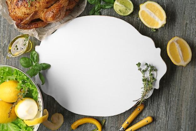 Komposition mit weißer tafel, gebratenem truthahn und produkten auf holz