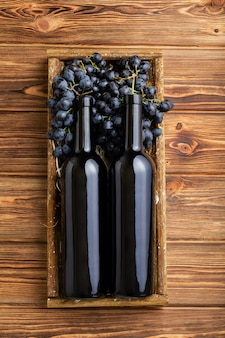 Komposition mit zwei rotweinflaschen auf braunem holztisch rotweinflaschen im karton auf schwarzen reifen trauben
