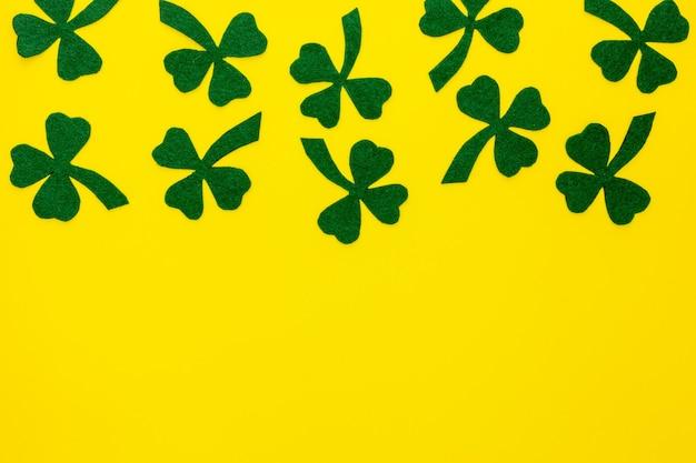 Komposition zum st. patrick's day. dekorpapier mit grünem klee oder kleeblättern und goldmünzen