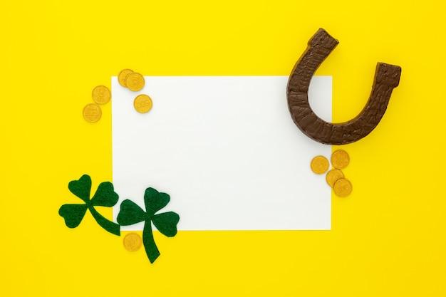 Komposition zum st. patrick's day. dekorpapier mit grünem klee oder kleeblatt, goldmünzen und hufeisen