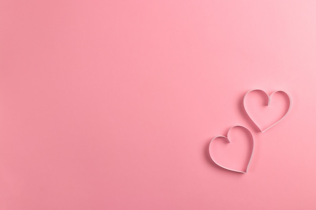 Komposition zum valentinstag februar. empfindlicher rosa hintergrund und rosa herzen schnitten vom papier heraus.