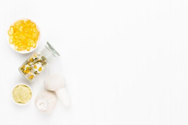 Kompositionsaromatherapie mit naturkosmetik und kamillenblüten auf hellem hintergrund.