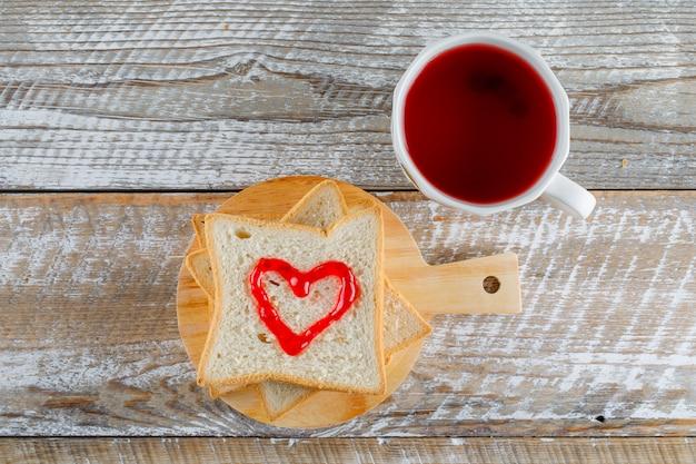 Kompott in einer tasse mit marmelade auf toastbrot flach auf holz und schneidebrett legen