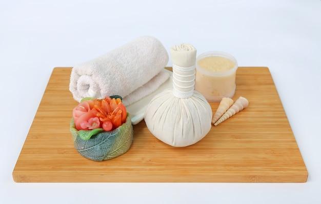 Komprimierender ball des badekurortes kräuter mit tüchern und salz scheuern sich gegen weißen hintergrund