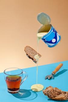 Kondensmilchpfütze fließt aus schwebendem glas, dosenöffner, schwarzbrot, glas schwarzem tee, konzeptfrühstück aus sowjetischer kindheit, vertikal, kopierraum, blauer und orangefarbener wand