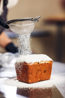 Konditor bestreut osterkuchen mit puderzucker durch sieb.