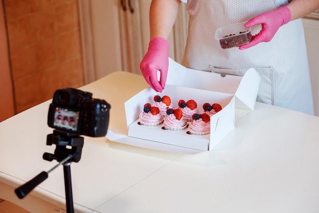 Konditor dekoriert cupcakes mit schokoladenstückchen und zeichnet sie vor der kamera auf
