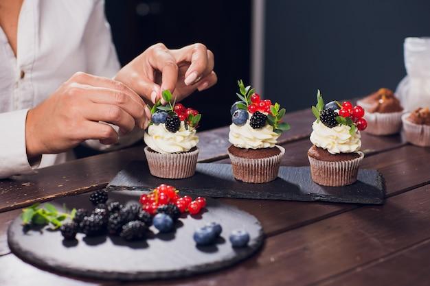 Konditor dekoriert den oberen cupcake vor dem servieren mit glasierter johannisbeere