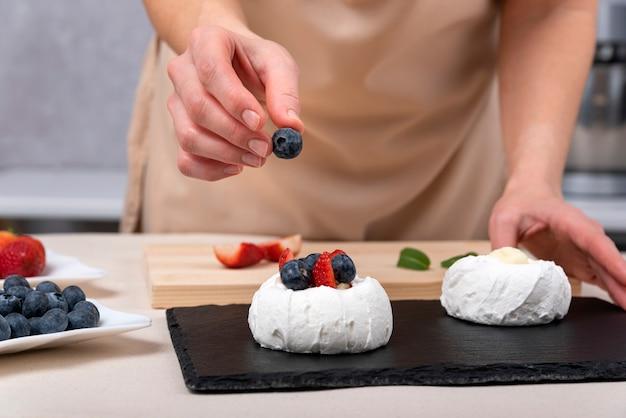 Konditor, der baiser mit blaubeeren und erdbeeren verziert. prozess der herstellung von kuchen.