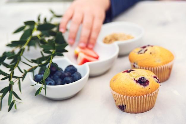 Konditor, der cupcakes verziert. kochkurs, küche und bäckerei.