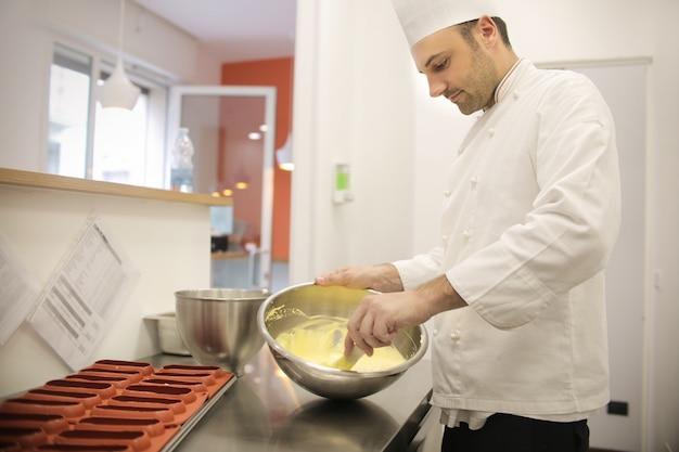 Konditor, der die sahne des kuchens zubereitet