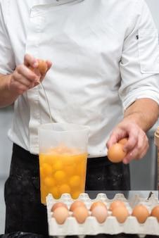 Konditor, der eier bricht, um den kuchen vorzubereiten