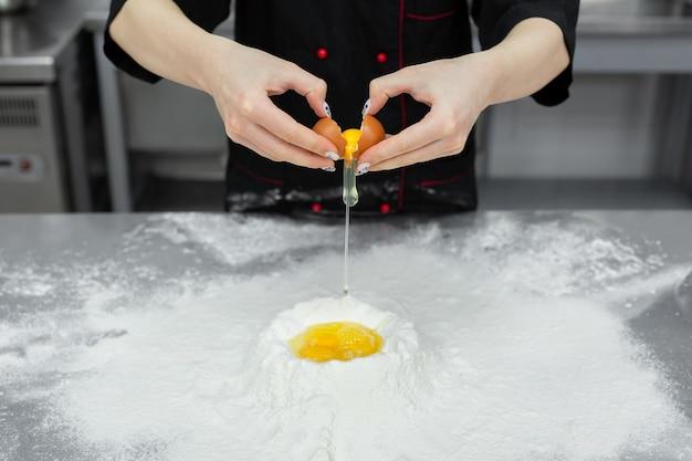 Konditor, der ein ei über weißmehl knackt
