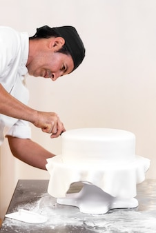 Konditor, der eine hochzeitstorte mit weißem fondant verziert.
